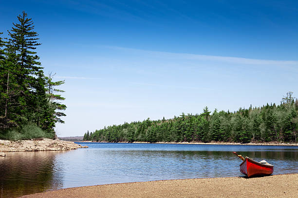 Red canoe stationed on a lake shore stock photo