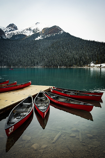Red canoes tied to a dock on Lake Louise, Banff National Park, Alberta, Canada in winter with snow capped mountains in background