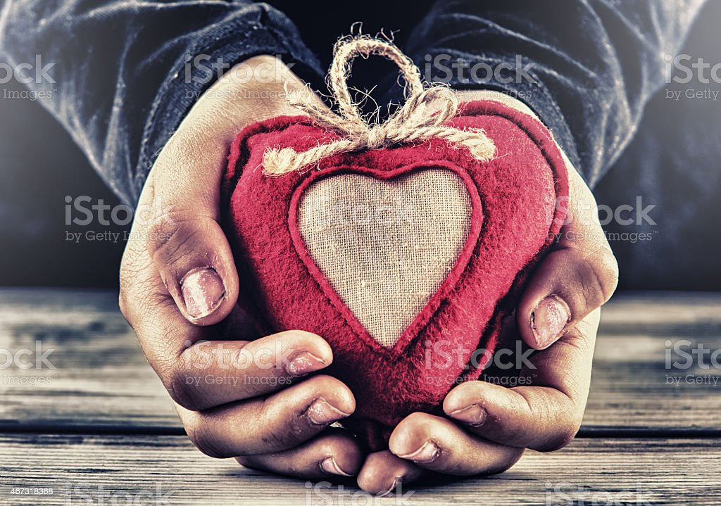 Red canvas valentine heart in the hands of a child. stock photo