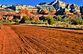 Red Canyon Road at sunrise.  After a rain the sandstone and subsequent sand all look more colorful.  Bear Mountain in background.  Sedona Arizona USA.
