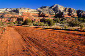 Red Canyon Road at Sunrise Sedona Arizona USA.  After rain the sandstone dirt becomes more colorful.  Bear Mountain in background.