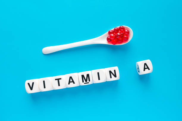 Red capsules in the white spoon and the word vitamin A from white cubes stock photo