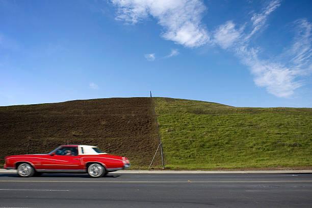 rotes auto und green hill - mark tantrum stock-fotos und bilder