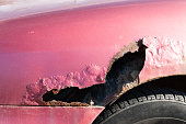 istock Red car broken side with damaged metal and hole, with rusty paint 903250312