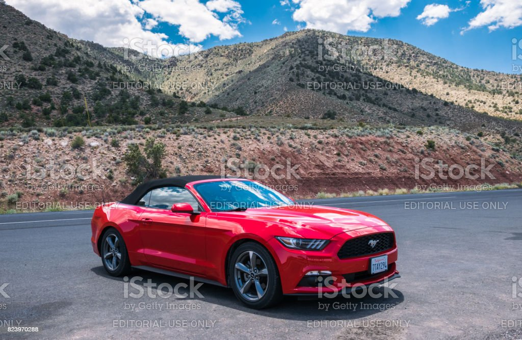 Red car cabriolet Ford Mustang and a desert landscape of Arizona stock photo