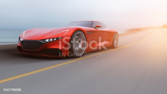 istock red car driving on a road by sea 1042759280
