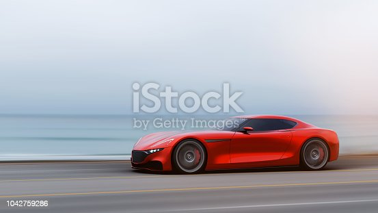 918555756 istock photo red car driving on a road by sea 1042759286