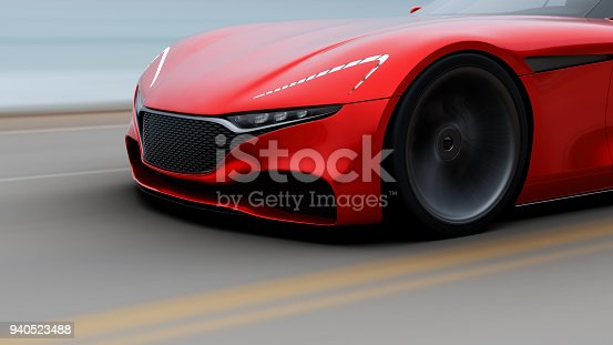 918555756 istock photo red car driving on a road by sea 940523488