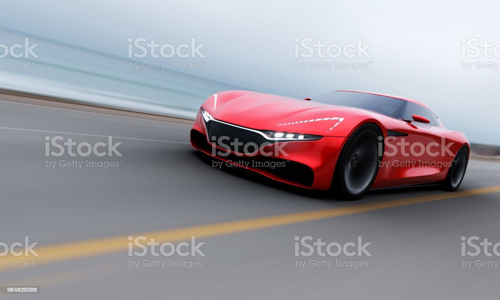 red car driving on a road by sea royalty-free stock photo