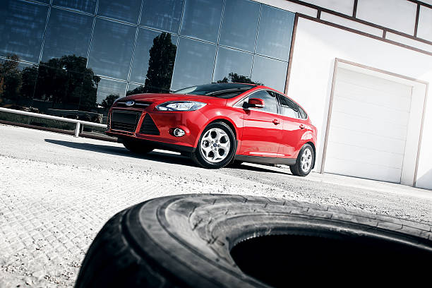 red car ford focus iii sport standing near mirror build - ford focus stock photos and pictures