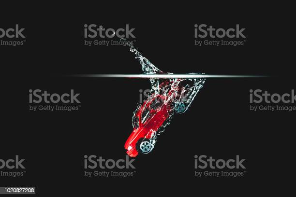 Photo of A red car hits the water, black background.