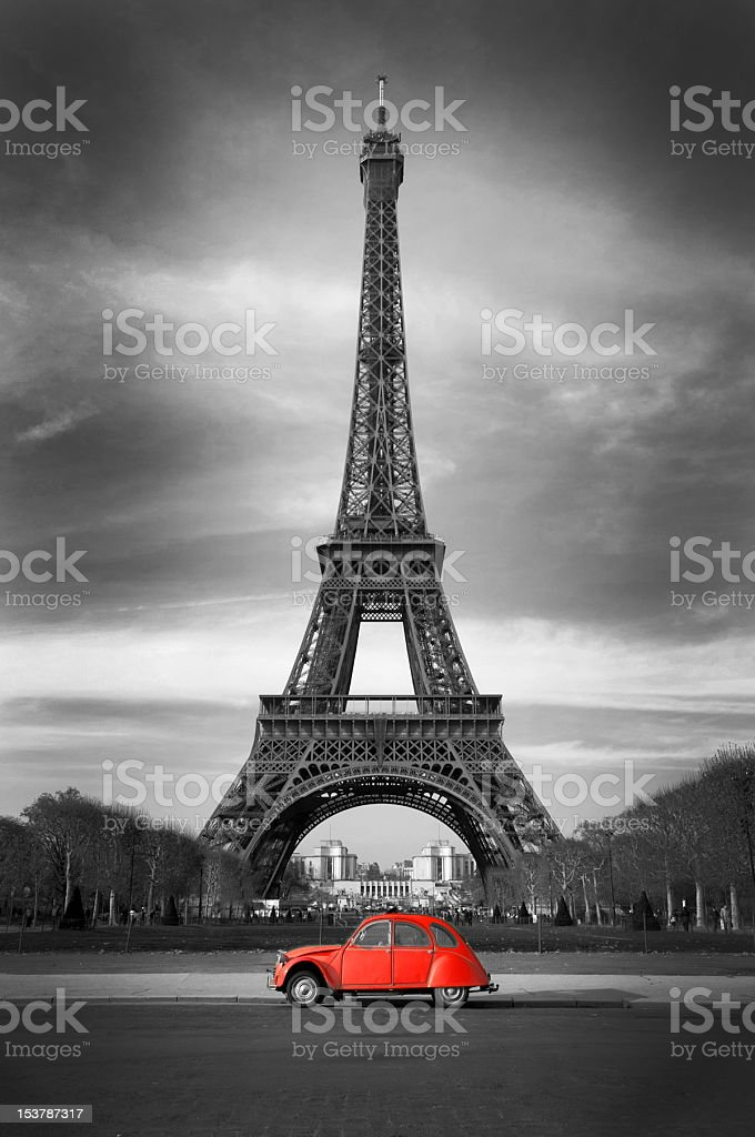 Red car in front of black and wite eiffel tower stock photo