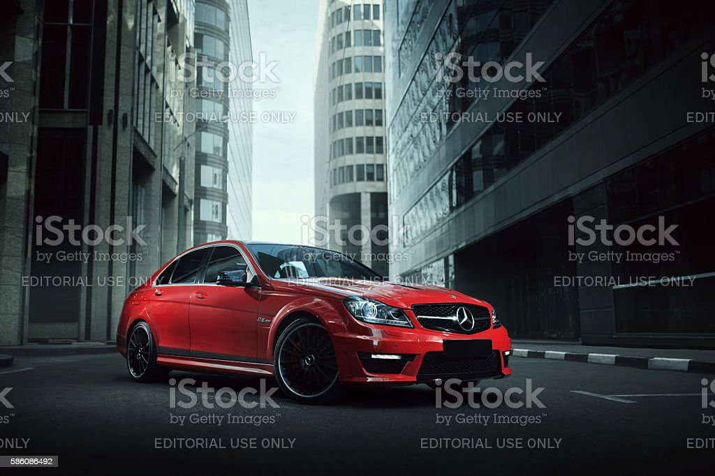 Red car Mercedes-Benz C63 stay on asphalt road in city Moscow, Russia - July 10, 2016: Red car Mercedes-Benz C63 AMG stay on asphalt road in the city Moscow at daytime Architecture Stock Photo
