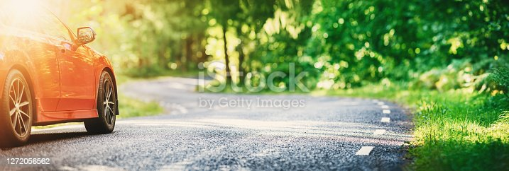 istock Red car on asphalt road in summer 1272056562
