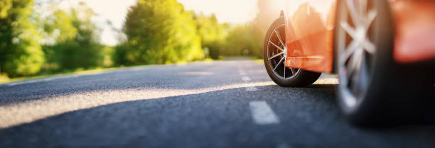 Red car on asphalt road in summer stock photo