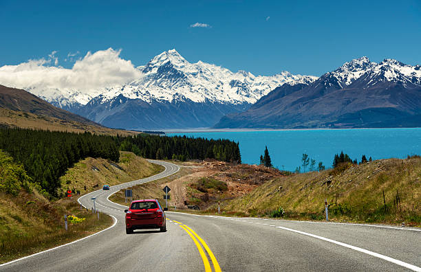 red car on the road to mt.cook,new zealand - nieuw zeeland stockfoto's en -beelden