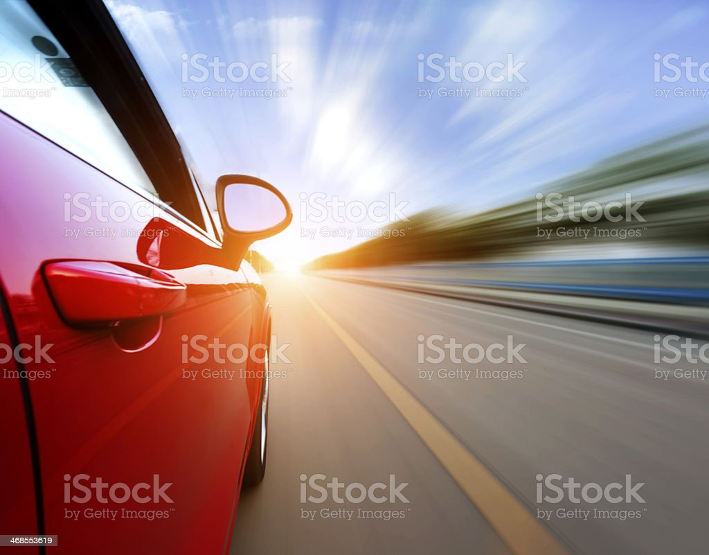 Red car on the road with a motion blur background stock photo