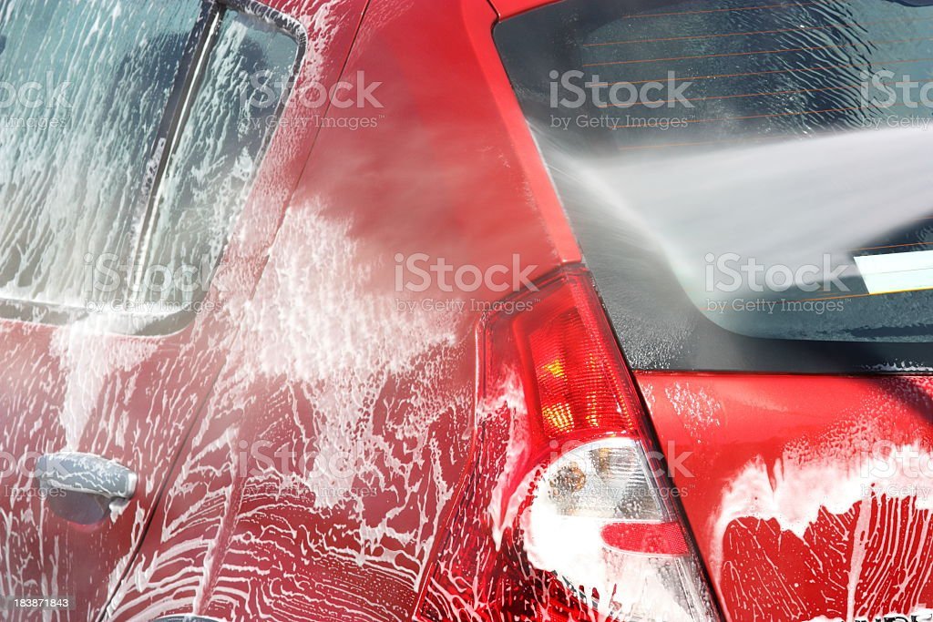 Red car undergoing a soapy car wash royalty-free stock photo