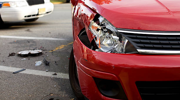 A red car with a damaged headlight after an accident Red Car in an Accident. Image Detail with Selective Focus. crash stock pictures, royalty-free photos & images