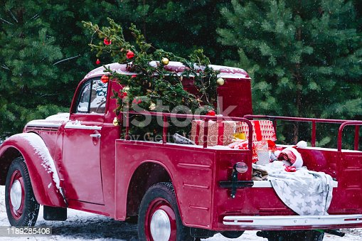 A red car with Christmas decorations and a Christmas tree is standing in a snowy winter forest. Festive New Year concept. Selective focus. Close-up. Horizontal frame