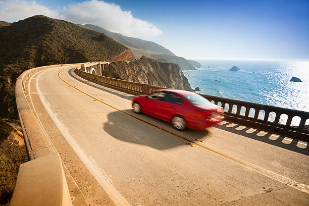 Red car zooms down Bixby Bridge in Big Sur stock photo