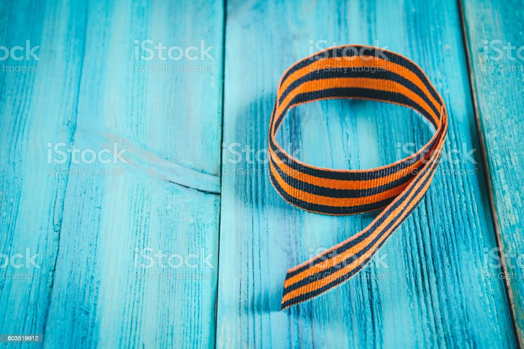 Red carnations and St. George ribbon on wooden background St. George ribbon - the symbol of the great Victory Victory Day stock photo