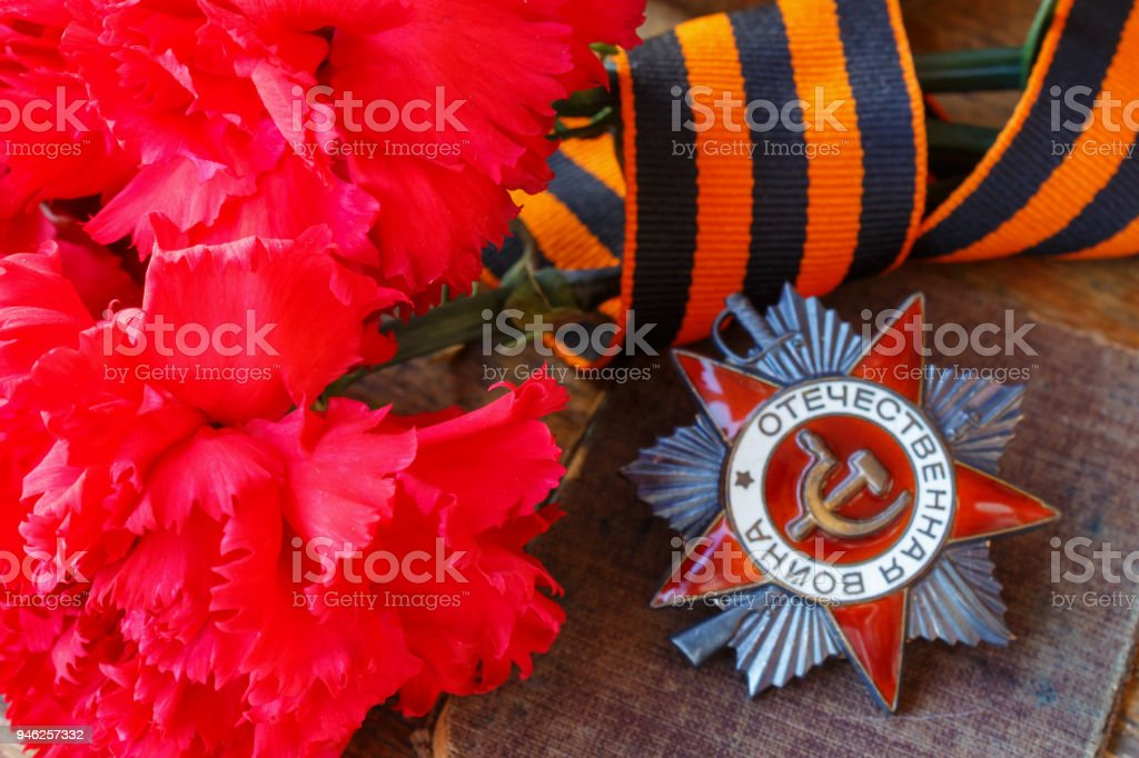 Red carnations with St. George's ribbon and Soviet order of Patriotic war (inscription Patriotic war) on an old wooden table. May 9 Victory day in the great Patriotic war of 1941-1945 stock photo