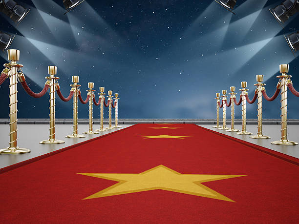 Red carpet and sky lit by spotlights Red carpet, velvet ropes and night lit by spotlights. walk of fame stock pictures, royalty-free photos & images