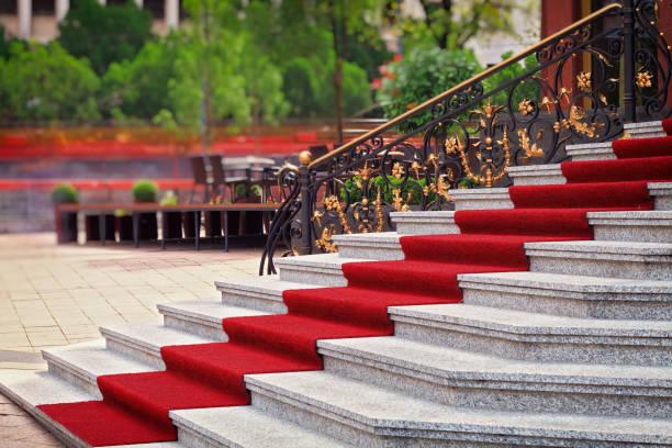 roter teppich auf treppe - eingangsbereich teppich stock-fotos und bilder