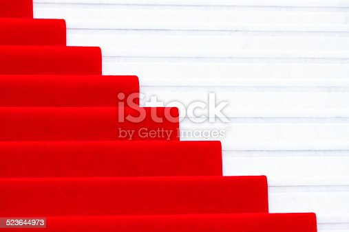 Close up red carpet on a white marble stairway used to mark the route taken by heads of state, vips and celebrities on ceremonial and formal occasions or events, full frame horizontial composition with copy space