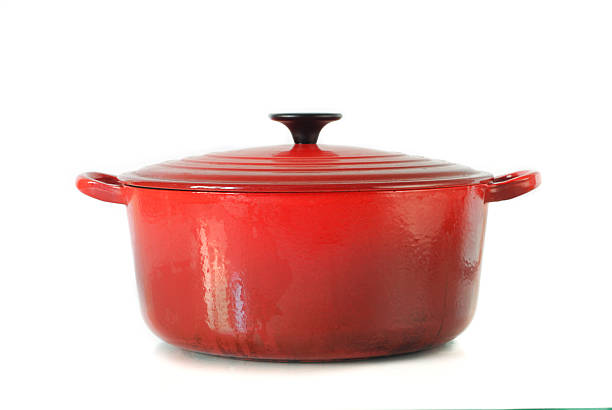red casserole dish on white background - kookgerei stockfoto's en -beelden