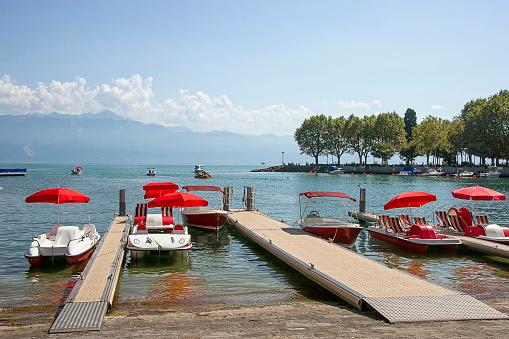 Red catamarans in Geneva lake bay harbor in Lausanne, Switzerlan