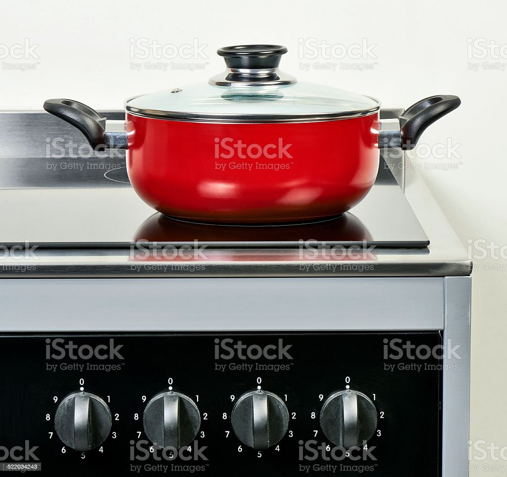 Red ceramic pan with cover on Electric hob stock photo