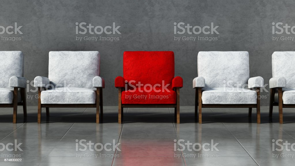 Red chair standing out among white chairs in a room stock photo