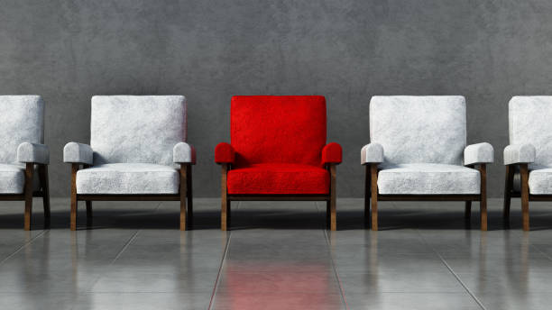 red chair standing out among white chairs in a room - contrasts stock pictures, royalty-free photos & images