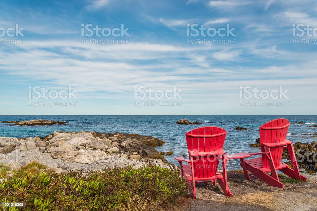 Red chairs facing Keji Seaside beach (South Shore, Nova Scotia, stock photo