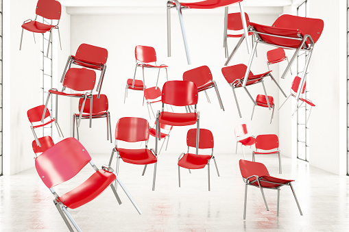 Red chairs float in the air. Surreal concept