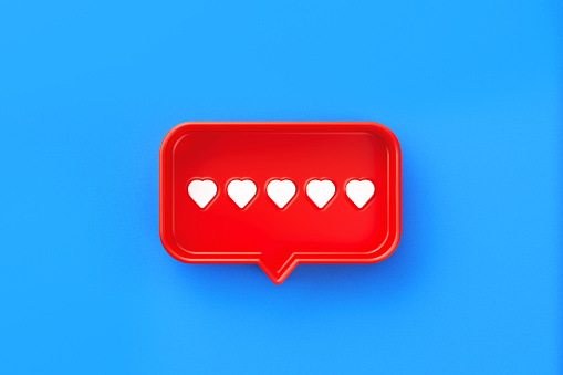 Red chat bubble with heart symbols inside on blue background. Horizontal composition with copy space. Rating and survey concept.