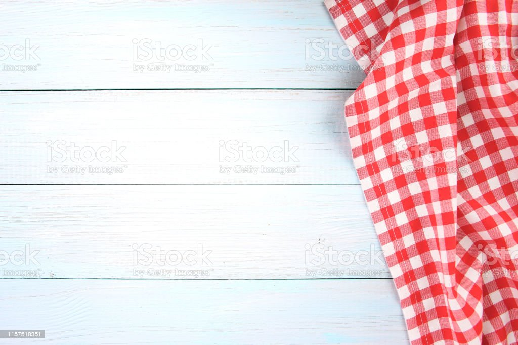 Red picnic checkered towel cloth on blue wooden background empty copy...
