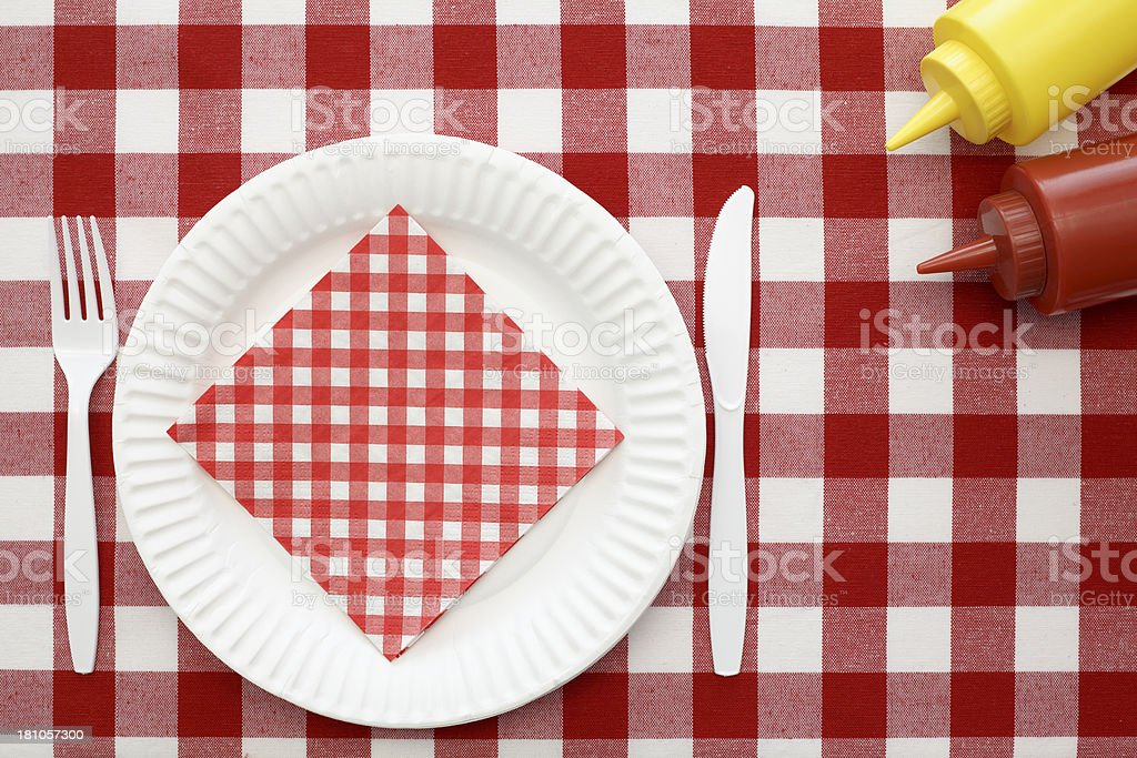 Red and white tablecloth with bottles of ketchup and mustard