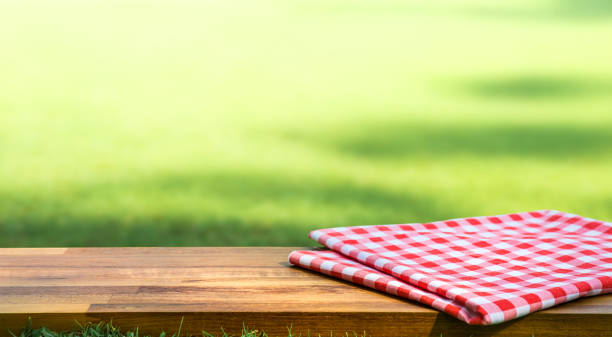 Red checked tablecloth on wood with blur green courtyard background.Summer and picnic concepts stock photo