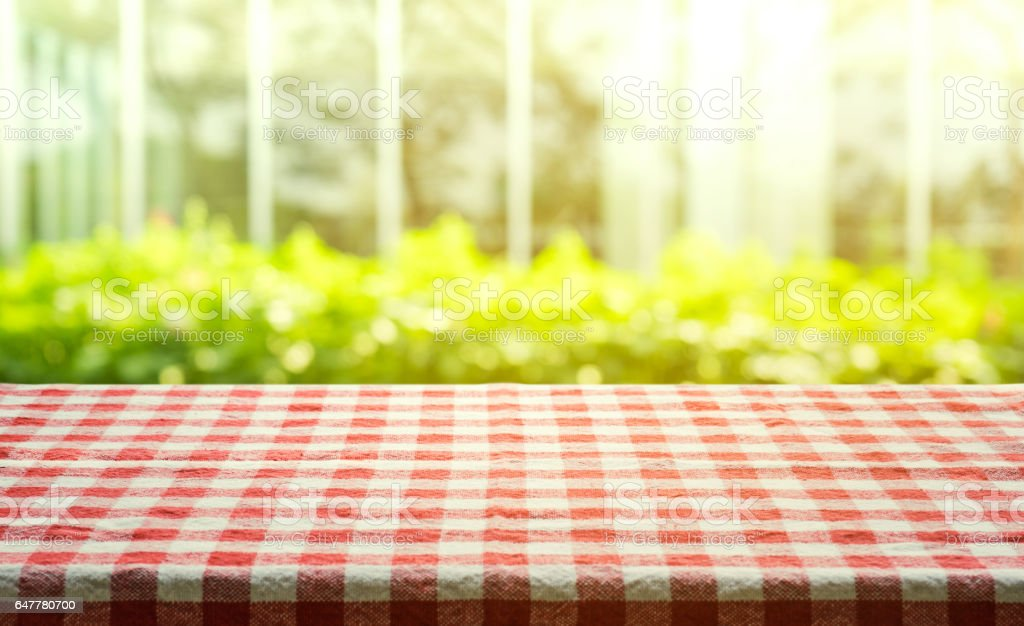 Red checkered tablecloth on abstract green garden morning background. stock photo