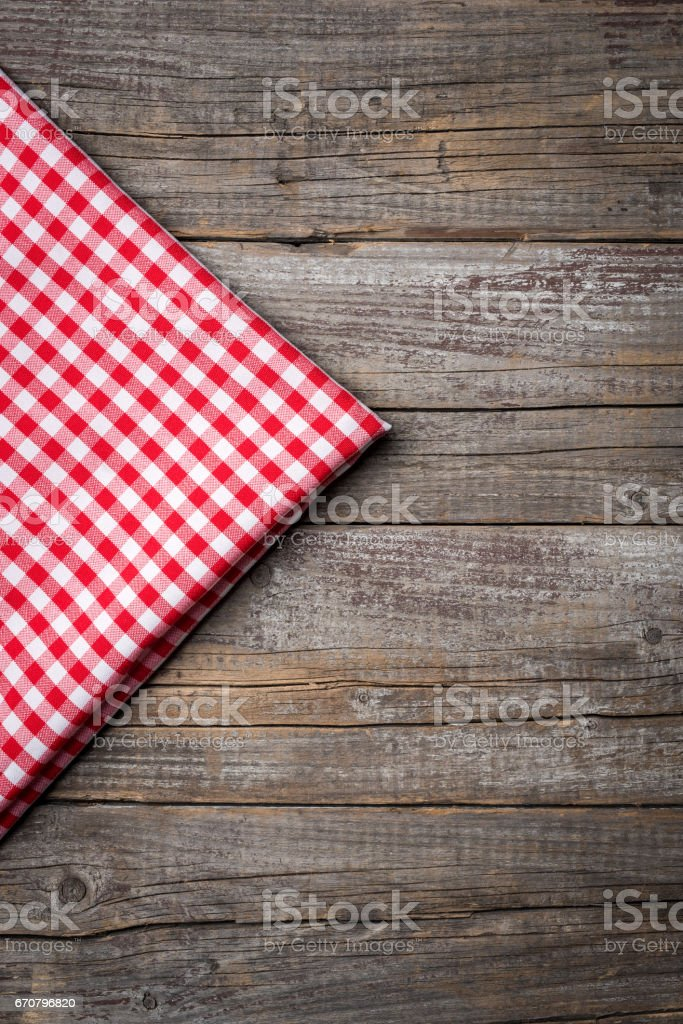 Red checkered tablecloth on wooden table with copyspace. stock photo