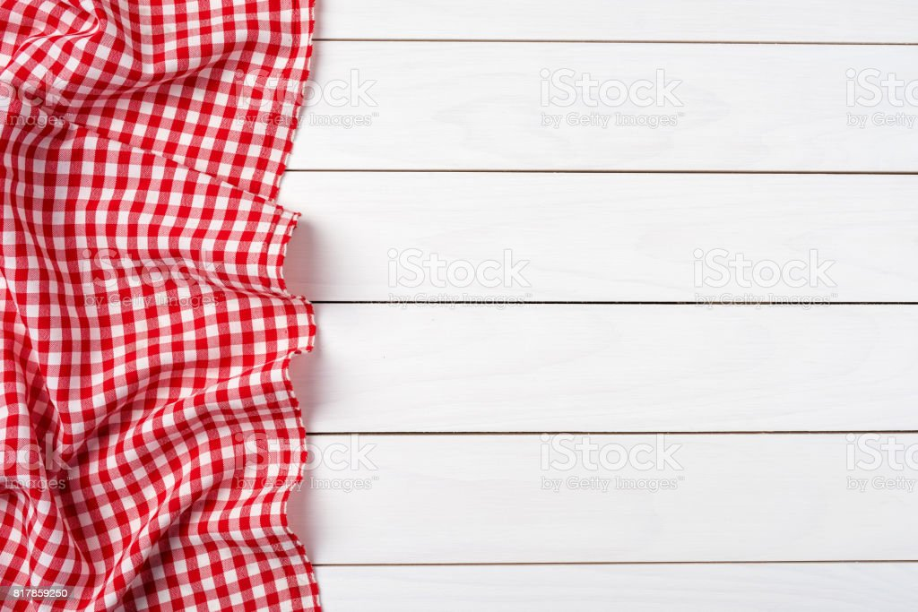 Red checkered tablecloth over white wooden table stock photo