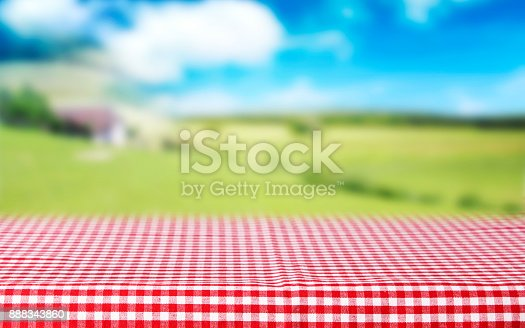 Red checkered tablecloth top view.Picnic table cloth blurred green field background.