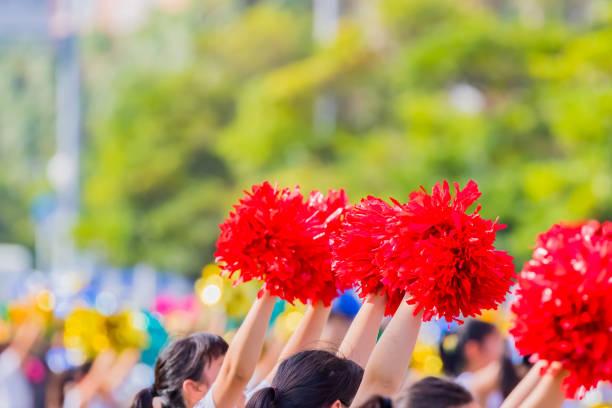 rode cheerleader pom poms - pompon stockfoto's en -beelden