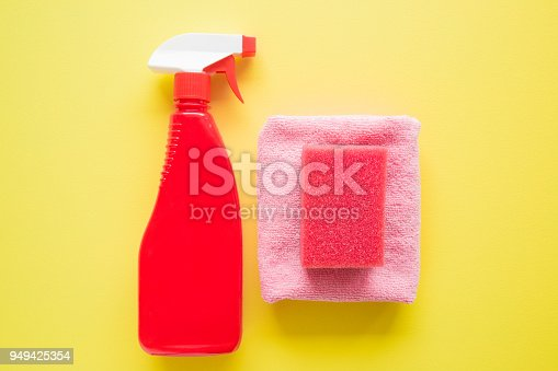 918825114 istock photo Red chemical spray bottle, sponge and microfiber rag for different surfaces cleaning in kitchen, bathroom and other rooms. Yellow background. Cleaning service concept. Early spring regular clean up. 949425354