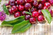 Red cherries. Juicy cherries on a wooden surface in the garden in a summer day. Sunny day. Sweet summer fruits. Shallow depth of field. Toned image. Copy space. Art photography.
