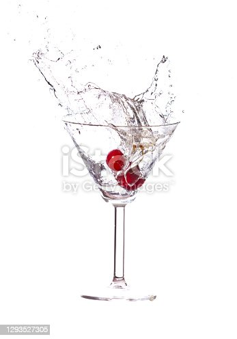 Red cherries splashing into a cocktail glass