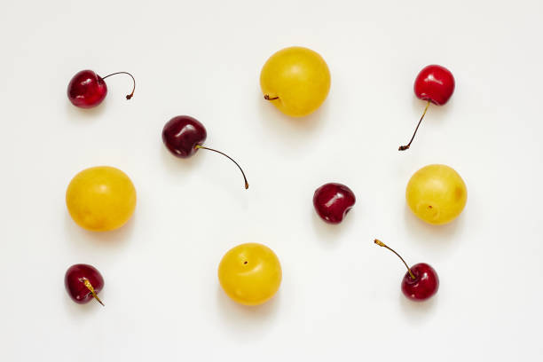Red cherry fruits and yellow plums over white background stock photo